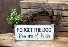 """This wood sign is made from pine, and measures Approx 5.5""""W x 13""""L. It reads """"Forget the Dog Beware of the Kids"""". The front is painted Craft White then distressed, the back is stained. We've used a pi"""