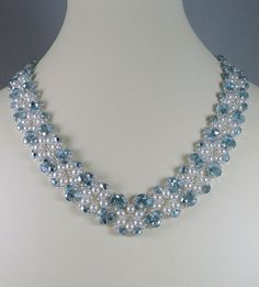Necklace with pearls and ice blue fire polished beads.  This hand woven V style necklace uses ice blue faceted glas fire polished beads white crystal pearls. Woven together with silver lined glass seed beads that give this piece a vintage look. The necklace measures 18.5 long with a pearl and rhinestone topped box clasp. Design by Debra Roberti.  https://www.etsy.com/shop/IndulgedGirl