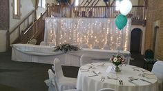 Silver swag and sashes, with white chair covers and backdrop, with silver and green balloons at Haselbury Mill