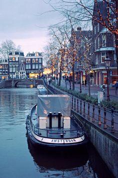 Sweet little serene scene of boat, water, fairy lights.