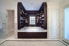 Built in shelving and a window surround this luxurious bathtub.