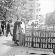 Pracownicy przy skrzynkach z butelkami mleka na rogu ul. Puławskiej i Olszewskiej. W tle widok ul. Olszewskiej w kierunku wschodnim.