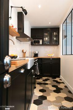 La cuisine accorde le carrelage dans un camaïeu de gris avec le reste de la cuisine très industrielle.