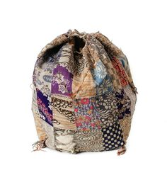 This is a delicate silk patchwork komebukuro or bag made for bringing  offerings of rice to temple or festival. Many different pieces of salvaged  or recycled silk chirimen or crepe fabric—over sixty different pieces—have  been skillfully hand stitched together with embroidered reinforcements and  tassels added. Floral, geometric, and nature themed patterns can be found,  many of which have been dyed with a botanical dye. The base of the bag is a  single piece of silk brocade.  The bag is…