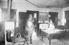 Recollections of domestic life. A 1910 kitchen with a lean-to pantry and a wood-burning stove. The sconces or reflectors on the kerosene lamps intensified the light
