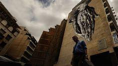 Daniel Ochoa de Olza/AP - Homem caminha entre prédios com um mural inspirado na obra do artista renascentista Albrecht Durer, em Atenas. Foto: Daniel Ochoa de Olza/AP