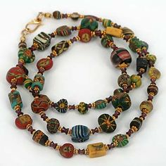 Collectible Ancient World Mosaic Glass Beads. Exquisite miniature masterpieces of ancient glass bead making from the first century AD onwards. Our very best beads in this category, in between garnet is also old. Gold is 18K.