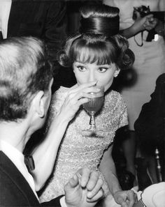 """The actress Audrey Hepburn photographed (next to her husband Mel Ferrer) during a dinner offered after the premiere of the film """"The Longest Day"""" at Palais de Chaillot in Paris (France), on September 26, 1962."""