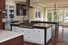Two tone cabinets, dark wood flooring and stainless steel appliances in a bright eclectic kitchen.