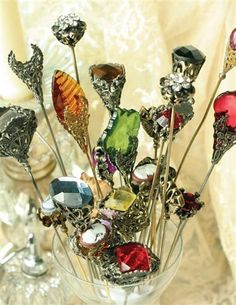 """A bouquet of century-old hat pins experience a renaissance when they are articulately cast, plated in antique finishes, and meticulously graced with hand-set crystals in a stained-glass palette. 8"""" lo"""