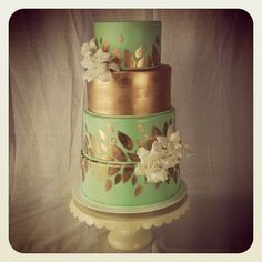 Mint and gold painted wedding cake  gold tier and gold painted leaves on the additional tiers.  White flowers