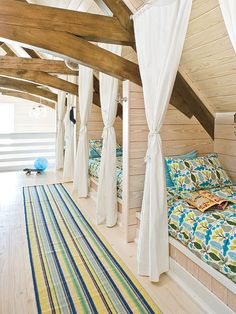 The top level of this home was just the right place for a children's loft and playroom. Train-style bunks built into the eaves create intimate little spaces for sleepovers. The playful bedding adds color and a bit of personality.