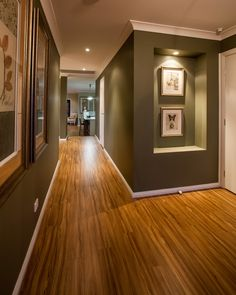 This hallway is full or artwork and recessed walls with feature lights