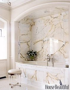 """A Marble Bathroom:   Designer Nancy Boszhardt said, """"We were so lucky to come across this marble. It's no longer available and there was just enough for the master bathroom."""" The house originally had arches throughout, and Boszhardt restored that architectural feature."""