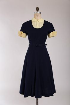Late 1940s vintage dress. Made of navy blue wool with removable yellow eyelet cotton trim. Peter pan collar, darted bust, fitted waist and full skirt. Closes with long back metal zipper. Original matching belt included. Purchased from the original owner. She sewed the dress in high school for her 4H and submitted it to the Oregon State Fair where it won in her group. It then went on to win the national level competition. The dress traveled through the country as a winner for two years. She…
