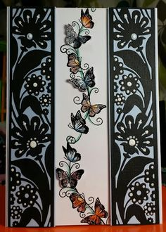 This card's two side panels were cut from black card stock w/ Tonic Studios' Aztec Allium die. One side was flipped, then both were mounted on light blue card stock & embellished w/ Tonic's Nuvo pearly drops.