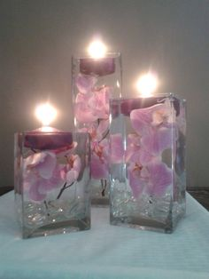 A set of three square vases with purple orchids floating in water perfect for unique wedding reception centerpieces or home decor