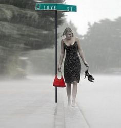 A really cool picture. I love how the rain is blurring the background and the splash of color with the purse and the street sign.
