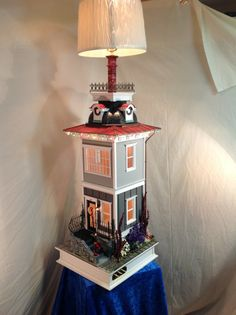 Bring the doll house into the family room with a gorgeous WORKING TABLE LAMP!  Miniature lighting system for the house as well. Interior and exterior.   Elouise is the queen of my lamps,.and has all the bells and whistles! She is a full two stories just waiting to be displayed in your home or office. she has the largest transformer available and is wired ,not only for holiday lights,..but has the capacity to add as many as 40 more lamps,sconces or table lamps,etc.  With true Victorian…