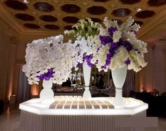 Escort card table with White porcelain vases filled with Colossal Blue Magic Vanda orchids, White Phaleonopsis orchid sprays & White Calla Lillies