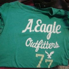 Green American Eagle Tshirt Good used condition.. with white and green lettering. Size XL. Sorry for the wrinkles as ive put some stuff in storage containers. American Eagle Outfitters Tops Tees - Short Sleeve