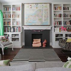 Living room. Bookshelves. Painted brick fireplace.