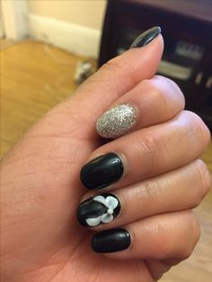Black and white nail design with a 3D bow detail.