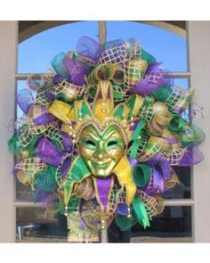 Mardi Gras Wreath, in purple, green, and gold colors, with layered metallic deco mesh spirals and accented with high quality coordinating wired ribbon, glitter ornaments and picks, and a large jester mask.