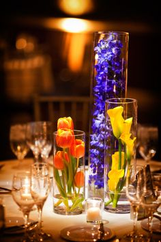 reception centerpiece details - blue, orange, and yellow flowers in glass vases - photo by Washington DC based wedding photographers Holland Photo Arts