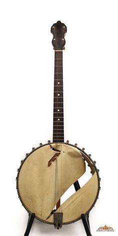 """This is an interesting and possibly prototypical Bacon banjo. It is an all maple, 17 fret open back with 11-1/2 rim with Silver Bell tonering. There is no markings on the dowel stick with the exception of a stampe """"X"""". The head is ripped and the banjo is dirty but not worn. The peghead shape is somewhat different than the typical Bacons. This would be great for Celtic style or convert to a five string."""