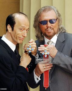 The two surviving members of the Bee Gees, Robin (L) and Barry Gibb hold their CBE's after receiving them from the Prince of Wales at Buckingham Palace, London, 27 May, 2004. The third brother, Maurice Gibb, died last year before he could receive the honour and so his son Adam collected it on his behalf.
