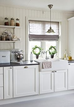 White kitchen, nickel finish pendant light in front of window