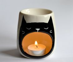 A yawning black cat candle holder that is a surefire reflection of you on the daily. | 38 Of The Cutest Animal-Themed Products You've Ever Seen