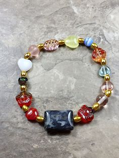 This precious bracelet is made with different colors Czech glass beads in a heart shape, gold metallic beads and square green stone in the center. The bracelet is measure approximately 8 inches. There