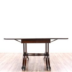 This Duncan Phyfe dining table is featured in a solid wood with a glossy mahogany finish. This European style kitchen table has 5 extendable leaves, tiny caster wheels, a long rounded rectangular top, and carved stretchers. Perfect for large gatherings! #european #tables #diningtable #sandiegovintage #vintagefurniture