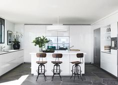In Courteney Cox's Trip Haenisch-designed home, wood-and-steel bar stools bring rustic flair to the all-white kitchen. Tour the entire home.