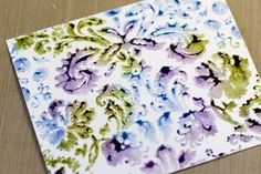 Leaving the stamp facing up on the table. Lay a piece of watercolor paper onto the inked stamp and press around. It is will messy and splotchy and yucky at first. But never fear – it will look lovely when it dries! (You can use regular cardstock. I just like the color of watercolor paper.)
