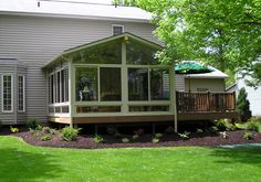 4 season sunroom with deck. Like the landscaping.