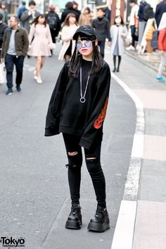 Maya is a 15-year-old Japanese high school student who we met on the famous Cat Street in Harajuku. Her all-black look features a flame print sweater from the Harajuku boutique a'gem Tokyo with ripped jeans by Rasvoa over fishnet stockings and Demonia platform shoes. Accessories – some of which came from Bubbles Harajuku – include a cap with safety pins, heart sunglasses, an o-ring necklace, and Basic Cotton tote bag. Maya's favorite shop is Never Mind the XU Harajuku and she likes the music…