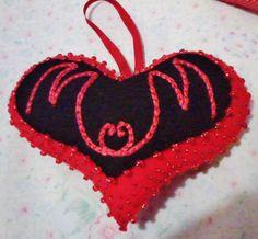 """corazón realizado en fieltro en colores rojo y negro con apliques de mostacillones y mostacillas y dos iniciales """"M"""" entrelazadas."""