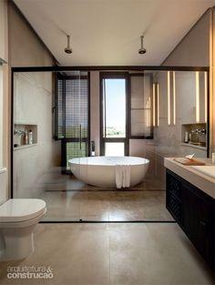 Impermeabilizadas, chapas (1 x 1 m) de arenito sandstone mate revestem, de cima a baixo, a sala de banho do casal. Discretos muxarabiês de c...