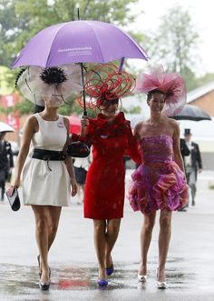 Women wearing ornate hats shelter under an umbrella on the third day, traditionally known as Ladies Day, of the Royal Ascot horse race meeting at Ascot, England, Thursday, June, 16, 2011.