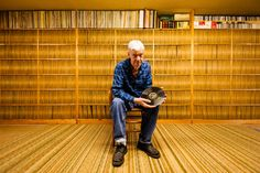 Joe Bussard sitting in his basement in Frederick, Maryland, with some of the rarest 78s in existence. The brown paper record jackets behind him are all uniformly discolored in the middle as a result of Joe's hands sorting and searching through them for the past 60 years.