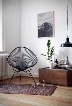 interior design living room with a sitting acapulco chair love the artwork and the industrial pendant light