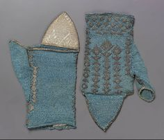 17th century, Italy - Pair of mitts - Knitted blue silk and silver. Five lengthwise bands of triangles and diamonds on back, one on front; triangles and diamonds across bottom of back. Ribbed silver flaps with figured motif.