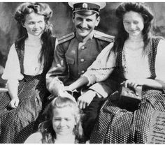 A fun photo of Olga, Tatiana and Marie, seated, with one of their trusted officers.