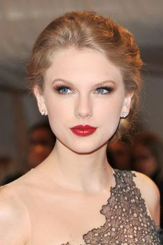 """Taylor Swift's Beauty Transformation - 2011: Swift went for an elegant updo and crimson lips for the MET Costume Institute's Gala for """"Alexander McQueen: Savage Beauty""""."""