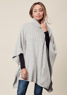 Oversized turtleneck poncho featuring two pocket detail and ribbed knit accents…