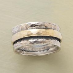 """A hammered 14kt gold band slides smoothly in the channel of a broad sterling silver band, also hammered. Whole and half sizes 6 to 9-1/2. 3/8""""W. This ring is licensed under U.S. Patent Nos. 6,497,117 and 6,395,732."""