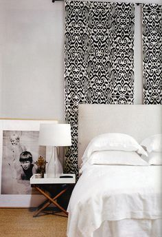 Why dont you hang a few panels of fabric behind your bed to add interest and height to your bedroom walls?